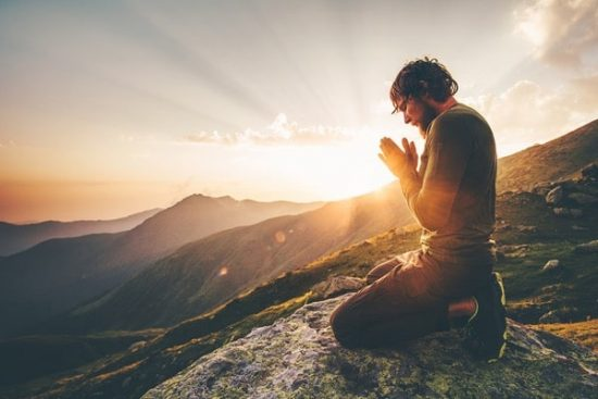 Bidden en mediteren bij een ondergaande zon in de bergen
