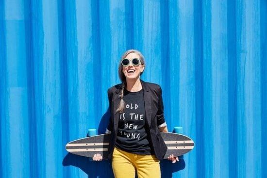 Vrouw met skateboard tegen een blauwe achtergrond