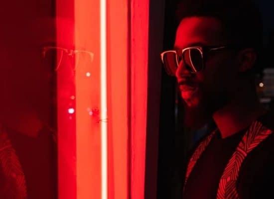 Man staat voor een raam met neonlicht