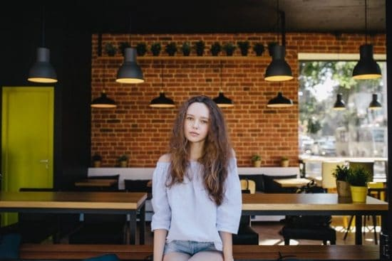 Meisje met krullend haar zittend op een tafel in een eetcafe