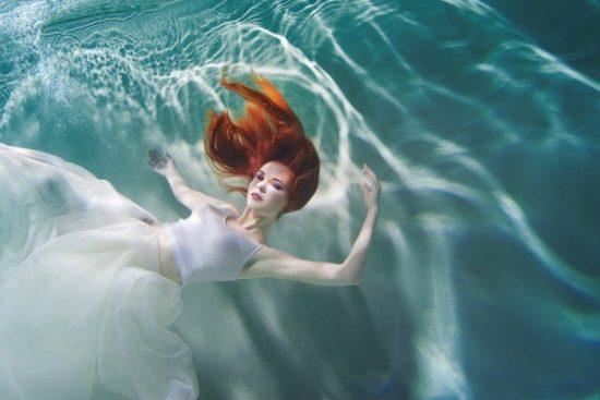 Jonge vrouw in witte jurk in het water