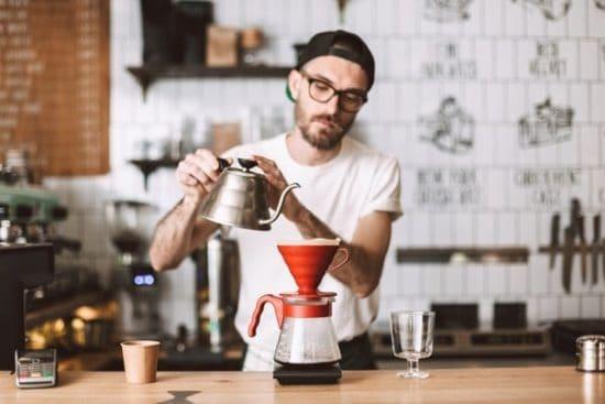 Man schenkt heet water bij voor verse koffie