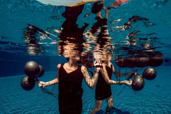 Vvrouwen staan gekleed in zwembad met ballonnen