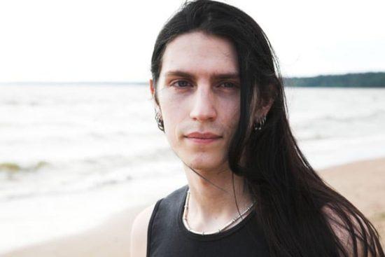 Jonge man met lang haar op strand
