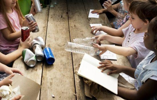 Kinderen knutselen aan een houten tafel