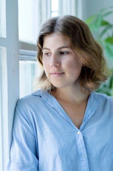 Jonge vrouw die door het raam naar buiten kijkt