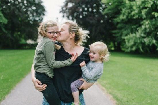Jonge moeder met kinderen op de arm