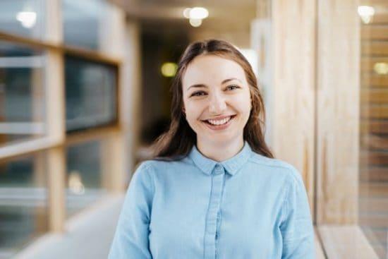 Jonge vrouw kijkt met brede glimlach in de camera