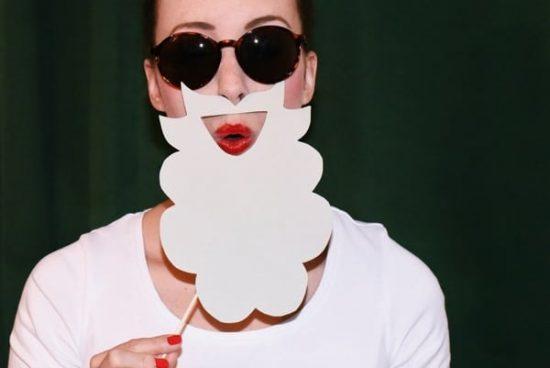 Vrouw met zonnebril en een baard van papier