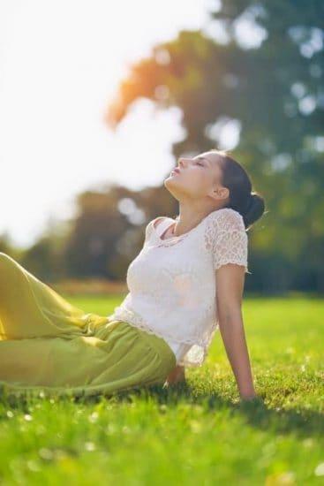 Vrouw zit ontspannen in het gras en geniet van de zon