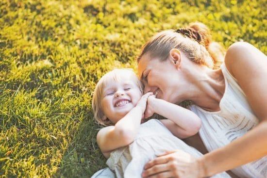 Gelukkige moeder met kind liggend in het gras