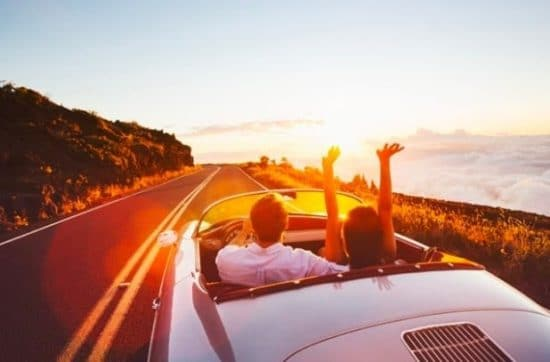 Stel in een cabrio op weg naar zonsondergang