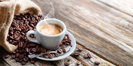 Kopje espresso met koffiebonen op een ouderwetse houten tafel