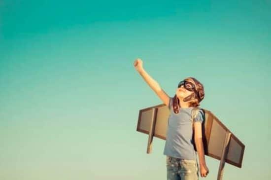 Blij kind dat in zelfgemaakt vliegtuigkostuum buiten speelt