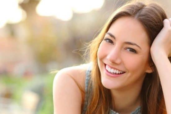 Portret van een jonge, lachende vrouw in de buitenlucht