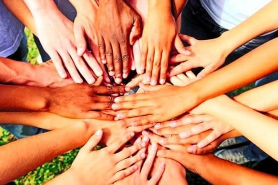 Veel handen op elkaar in een kring