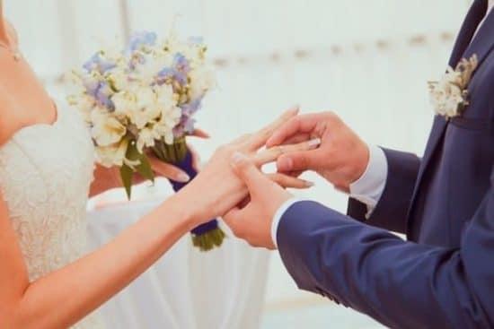 Bruidegom schuift zijn bruid een ring om haar vinger