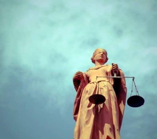 Vrouwe justitia met bewolkte lucht