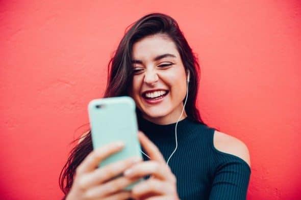 Photocase Jonge met smartphone tegen een rode achtergrond