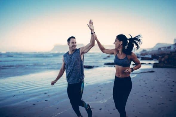Photocase Jong stel aan het joggen op het strand elkaar een high five gevend