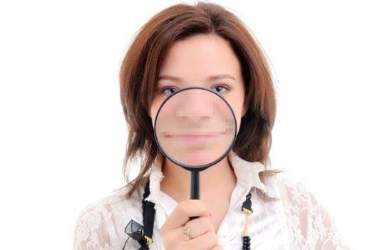 Vrouw kijkt door vergrootglas - posters printen