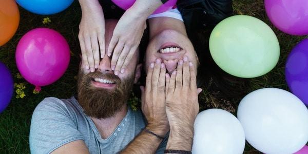 Photocase hipster stel ligt tussen ballonnen met handen op elkaars ogen