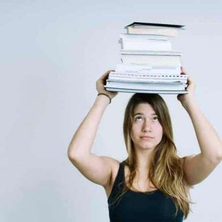Jonge vrouw met een stapel huiswerk op haar hoofd