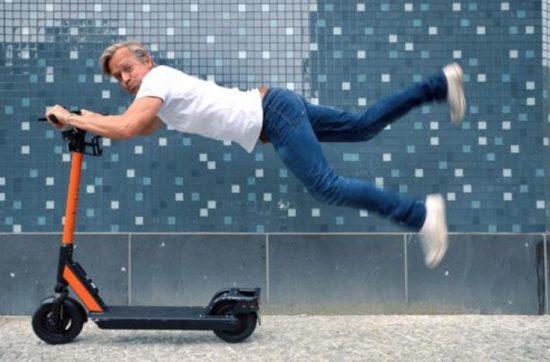 Man wordt achter een elektrische step aangesleurd