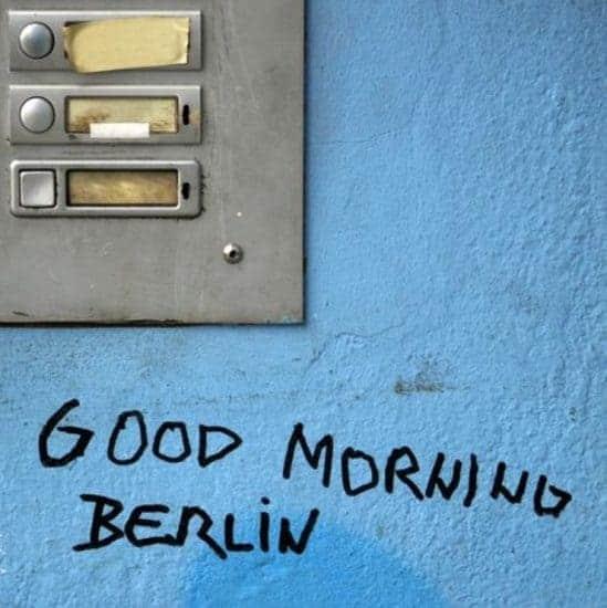 Blauwe muur met deurbellen en tekst