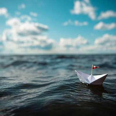 Papieren bootje op zee met wolken aan de horizon