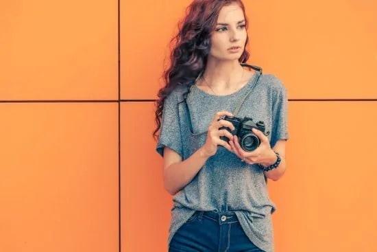 Jonge vrouw met camera tegen oranje achtergrond