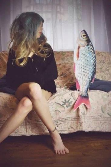 Jonge vrouw zit op de bank met vis naast zich