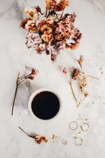 Kopje koffie op een mer droogbloemen versierde tafel