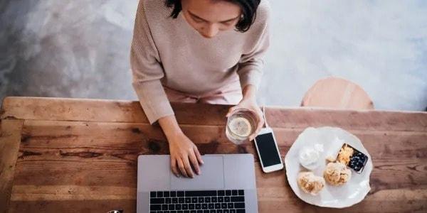 Vrouw achter haar laptop met een lekker ontbijt