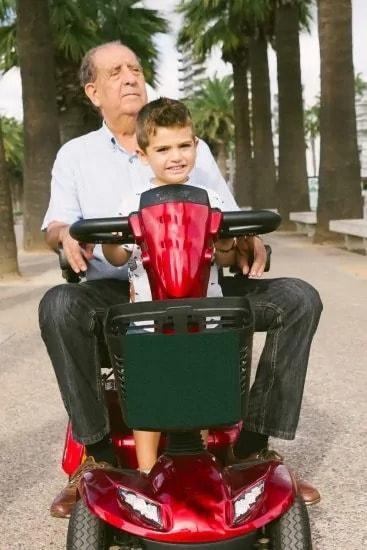Opa met een kleinzoon op de scootmobiel