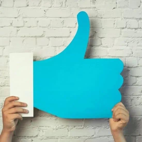 Twee handen houden een duim omhoog icoon op - geen waardeloze stockfoto