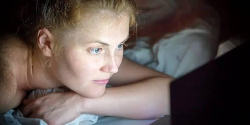 Jonge vrouw kijkt op haar laptop in bed