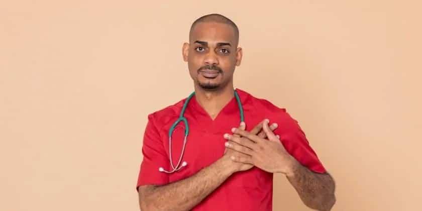 Jonge arts met handen op zijn hart