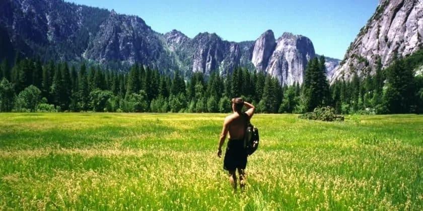 Jonge man maakt wandeling in een bergweide