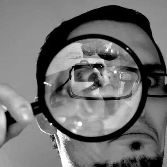 Close up van een man die door een vergrootglas kijkt