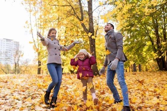 Gezin maakt plezier met herfstbladeren