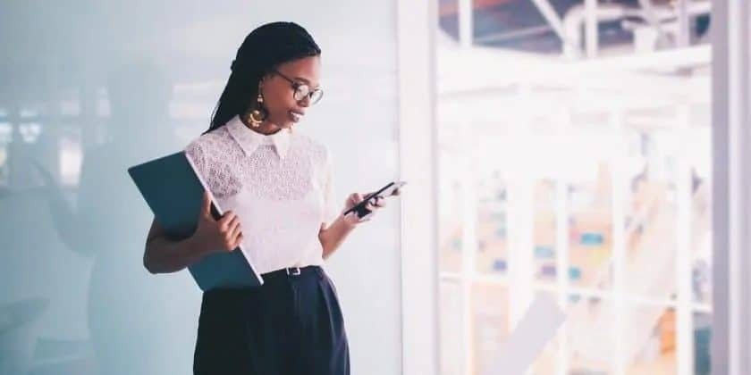 Jonge zakenvrouw leest berichten op haar smartphone