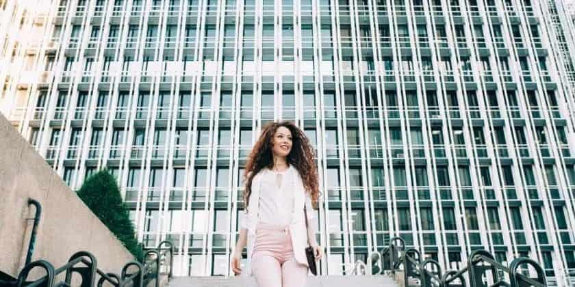 Jonge zakenvrouw met rood haar loopt de trap af