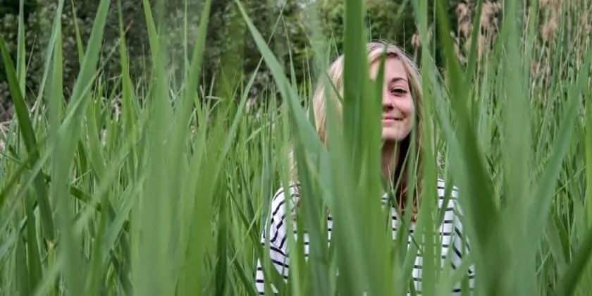 Jonge vrouw loopt glimlachend door het hoge gras