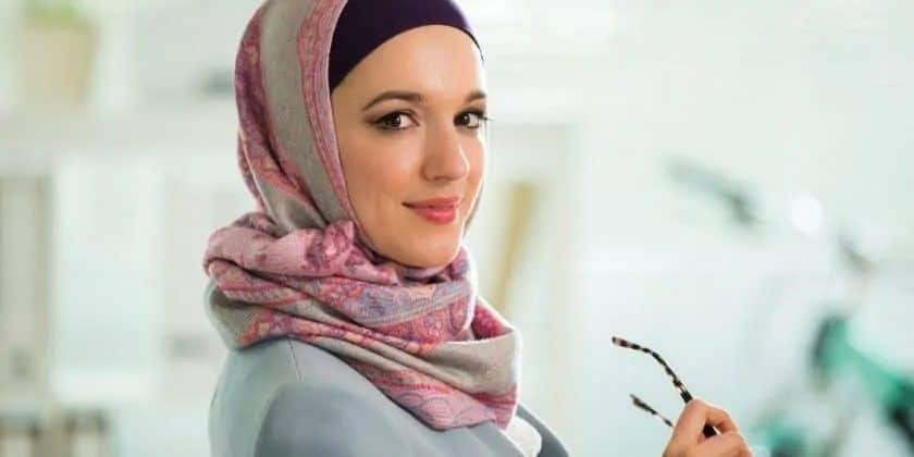 vrouw met hoofddoek kijkt met glimlach in de camera