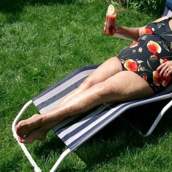 Vrouw met glas met koel sap op ligbed