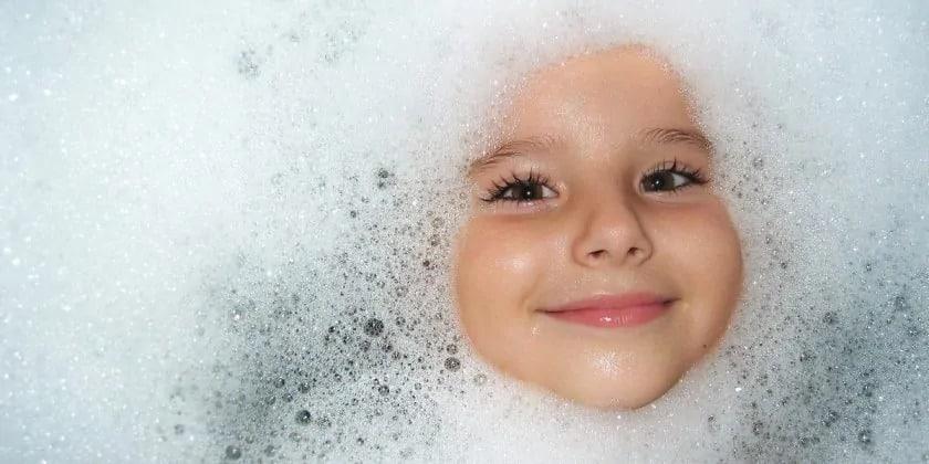 Kindergezicht in het badschuim