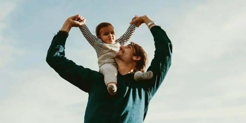 Jonge vader met kind op schouders