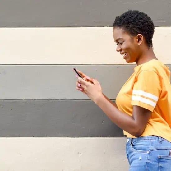 jonge vrouw met device als voorbeeld van Millennials stockfoto's